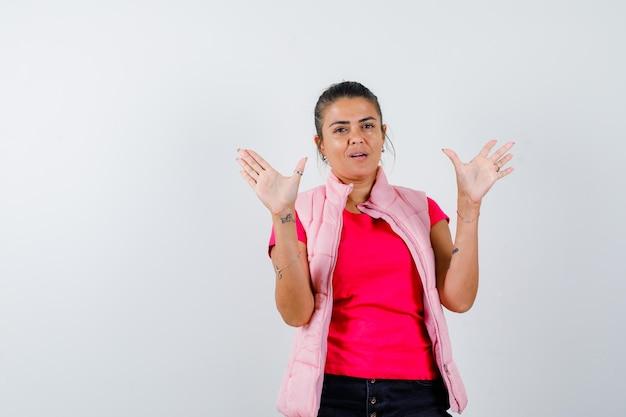 Tシャツを着た女性、空の手のひらを示し、自信を持って見えるベスト