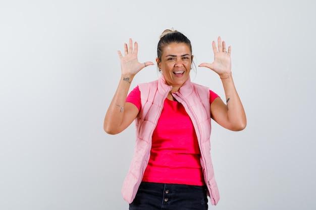 Tシャツを着た女性、空の手のひらを見せて幸せそうに見えるベスト