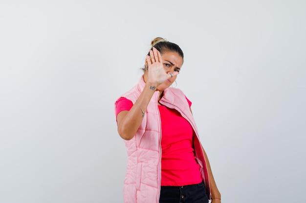Женщина в футболке, жилетке показывает жест остановки и выглядит раздраженной