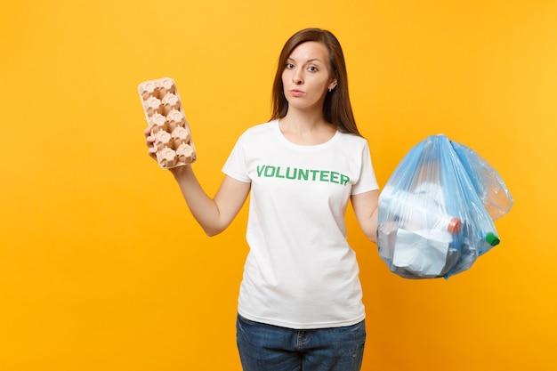 Tシャツボランティアの女性、黄色の背景で隔離のゴミ袋。自発的な無料援助の助け、慈善の恵み。環境汚染問題。自然ゴミ環境保護の概念を停止します。