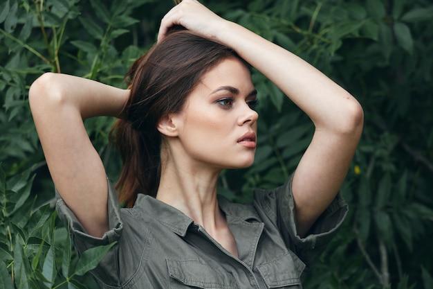 タイガの手で女性が頭の森の夏のトリミングされたビューで髪に触れる