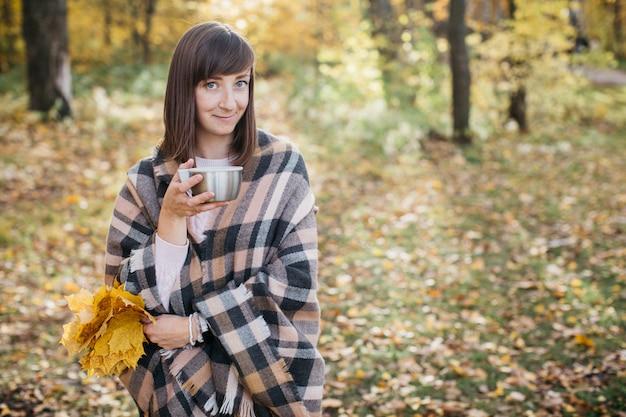 の手で葉とお茶を飲んで秋の森の女性。太陽