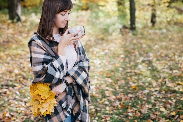 手に葉を持ってお茶を飲む秋の森の女性太陽