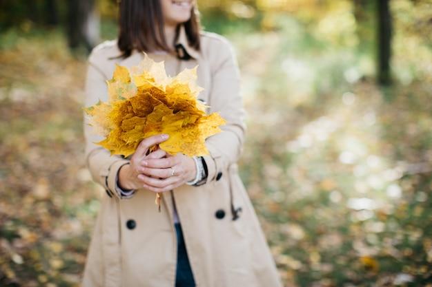 手に葉を持つ秋の森の女性女性は幸せです