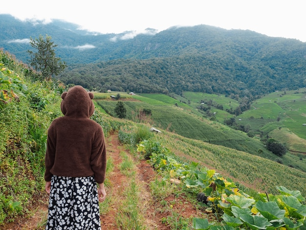 後ろの女性は、梅雨の季節、チェンマイ、タイのpabongpiang村で霧の曇り空と緑の農場の丘の上を歩く羽のセーターを着ています