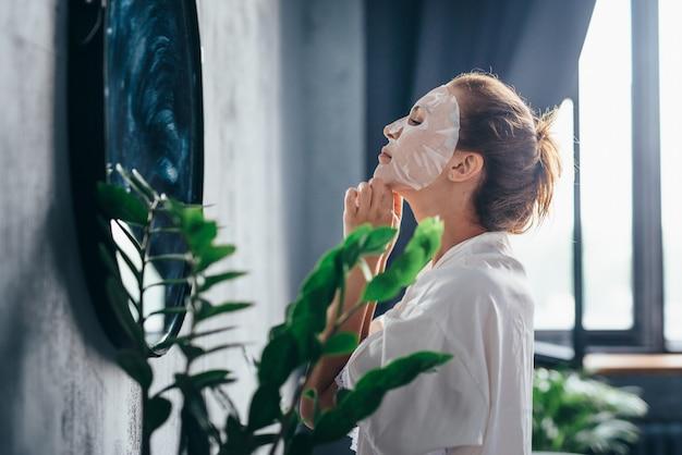 그녀의 얼굴에 마스크를 적용하여 그녀의 얼굴 피부를 돌보는 화장실에서 여자.