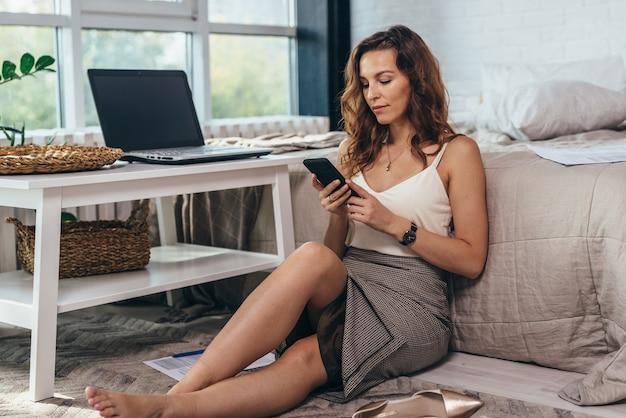 침실에있는 여자는 바닥에 앉아 스마트 폰 화면을보고 있습니다.