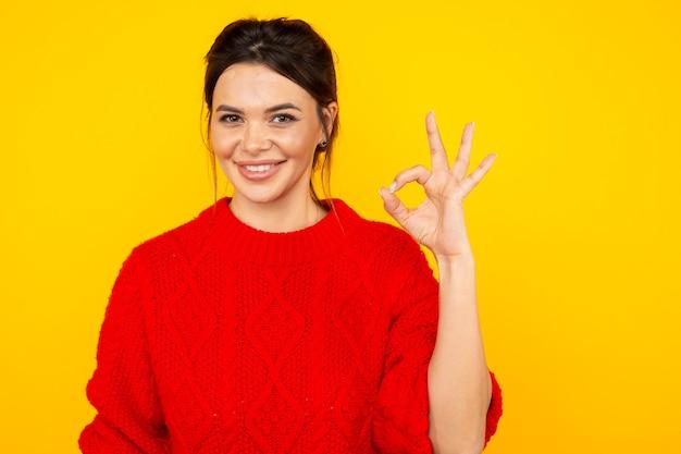 Женщина в ярком цветном свитере показывает знак ок.