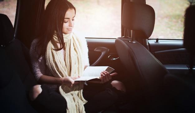 차에 있는 여자, 가을 컨셉입니다. 차에서 움직이는 책을 읽고 웃는 예쁜 여자