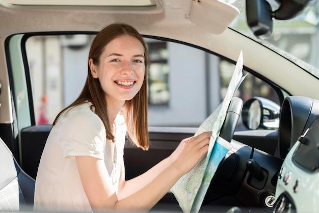 航海の地図を保持している車の中で女性