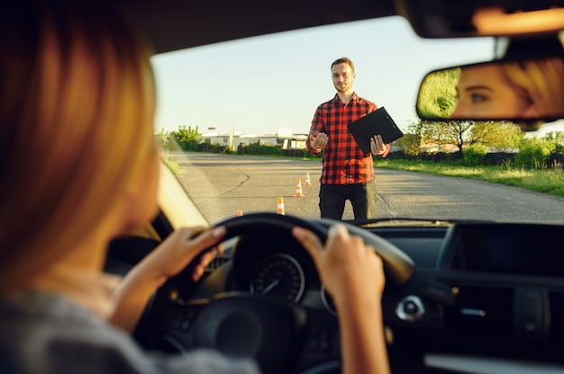 Женщина в машине, инструктор с контрольным списком на дороге, автошкола. мужчина учит леди водить автомобиль. образование водительского удостоверения