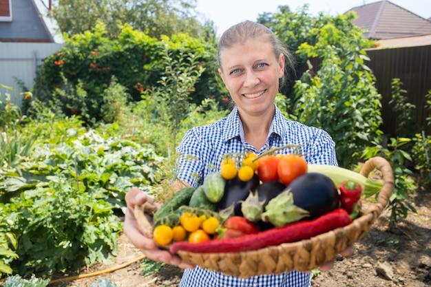 Женщина в деревне с урожаем овощей