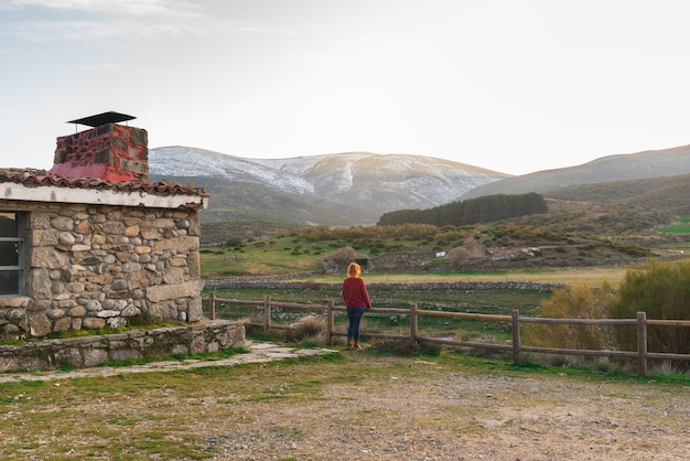 Женщина в дверях хижины смотрит на пейзаж с горами на заднем плане