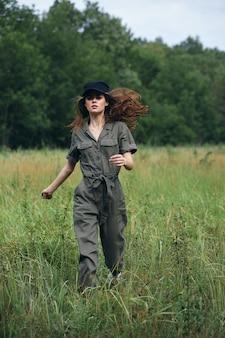 フィールドの女性草の旅でジョギングしている緑のジャンプスーツの黒い帽子