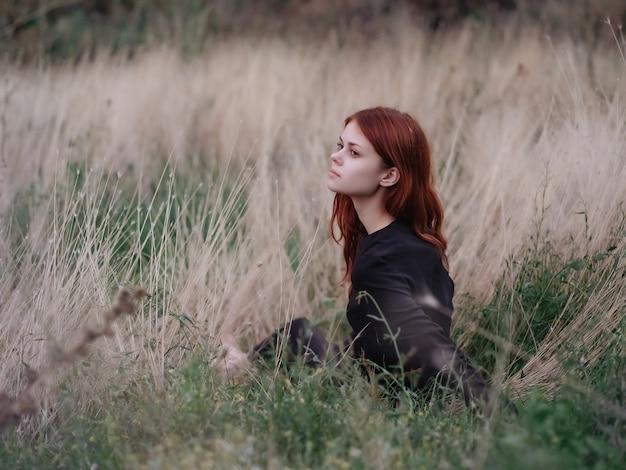 フィールドの女性は草の休暇の風景に横たわっています。高品質の写真