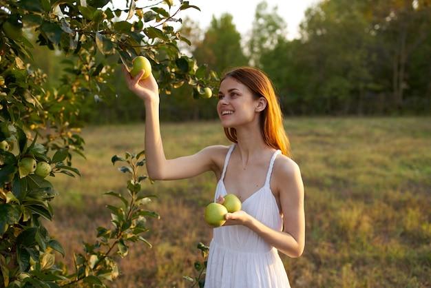 フィールドの女性太陽りんごフルーツ夏