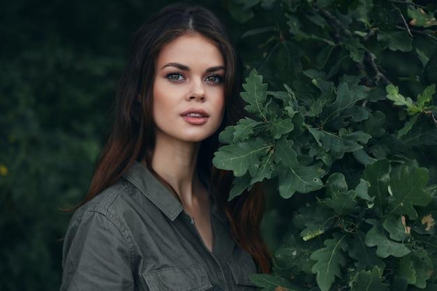 Женщина на фоне леса. зеленые листья кустарников крупным планом путешествия обрезанный вид