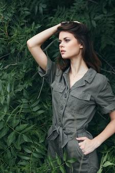 녹색 죄수 복의 숲에있는 여자는 그의 머리에 손을 잡고 옆 나무를 바라본다.
