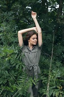 森の中の女性手を上げて緑のジャンプスーツで旅行クローズアップ