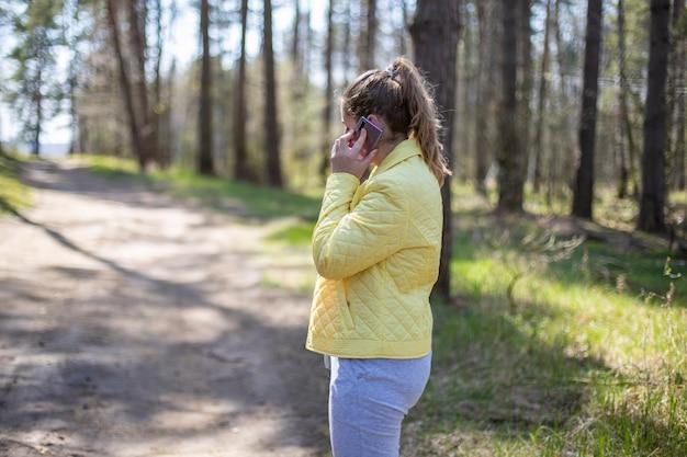 Женщина в лесу эмоционально разговаривает по телефону g концепция сотовой связи