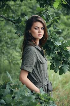 숲에서 여자 주머니에 손을 옆으로 봐 라이프 스타일 배경 녹색 잎
