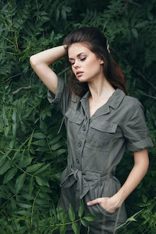 숲에있는 여자는 녹색 죄수 복 여행의 주머니에 손을 내려다보고