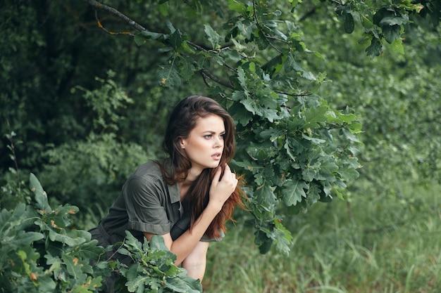 地面側のビューに座っている森の女性緑の葉のトリミングされたビュー