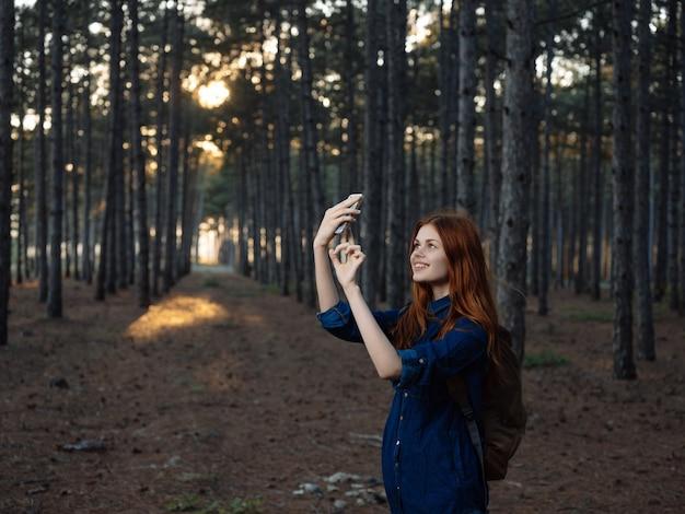 彼女の手に携帯電話を持っている森の女性は、休暇の観光旅行を旅行します。高品質の写真