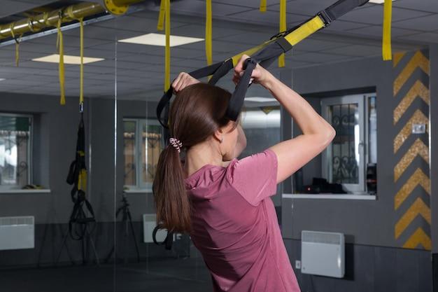 輪ゴムでtrxトレーナーに体重をかけてスポーツをしているジムの女性