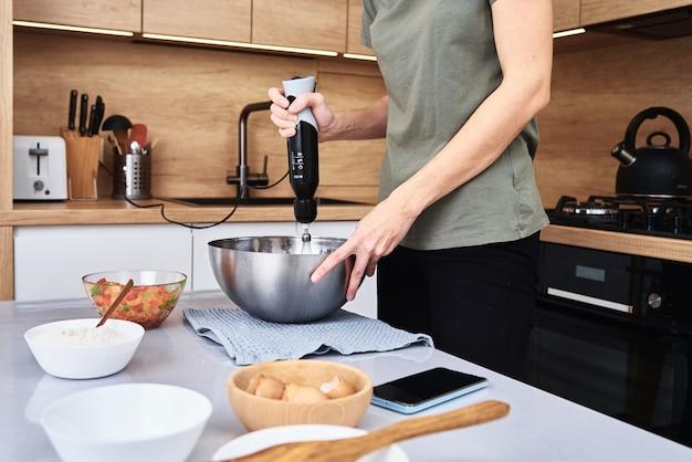 ケーキを調理するキッチンの女性。手が電気ミキサーで生地を叩く