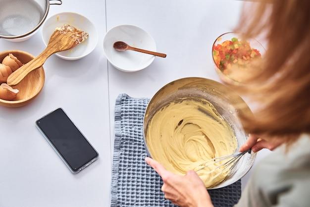 ケーキを調理するキッチンの女性。手がミキサーで生地を叩く