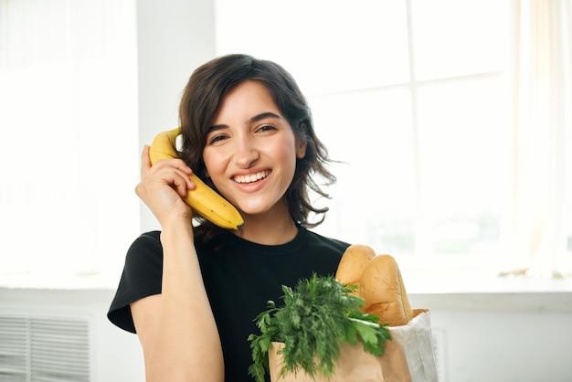 食品配達の健康を調理する食料品とキッチンパッケージの女性
