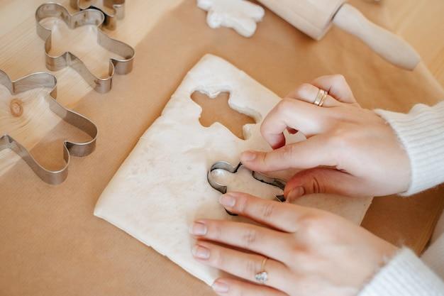 Женщина на кухне готовит рождественское имбирное печенье с помощью металлических форм в виде человечка. концепция выпечки к празднику рождества христова