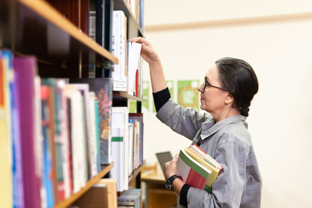 책장 앞 도서관에 있는 여자. 교육의 개념