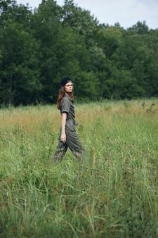 牧草地の女性自然は木の自由を背景に畑を歩く