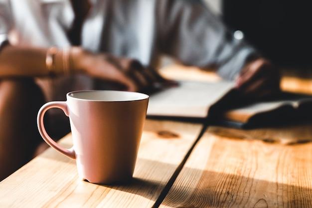 朝の女性はコーヒーを飲み、白いシャツで古い本を読みます。教育、飲み物。マニキュア