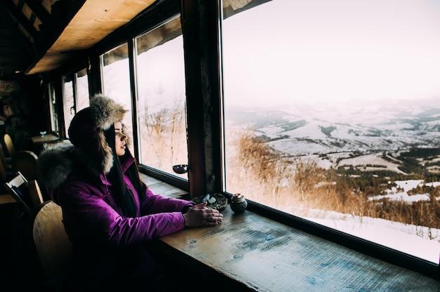 아침에 여자입니다. 산 전망 샬레 집에서 발코니에서 차 또는 커피를 마시는 알프스 산에서 맑은 아침을 즐기는 젊은 웃는 여자.