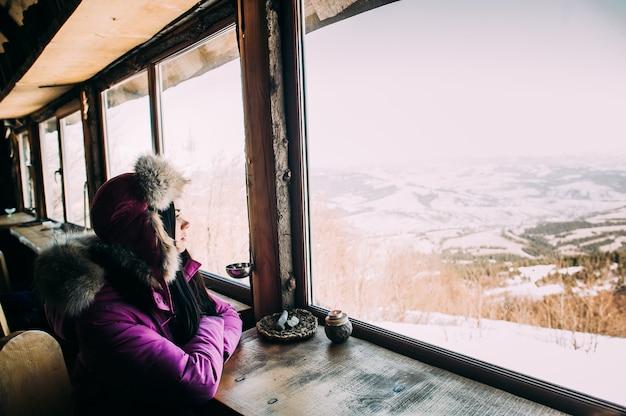 아침에 여자입니다. 차를 마시는 알프스 산맥에서 맑은 아침을 즐기는 젊은 웃는 여자
