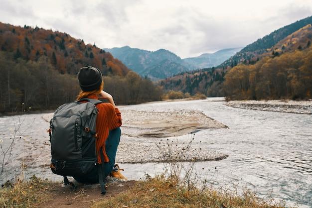 バックパックを背負って秋の山の女性川岸に座って高山を眺める