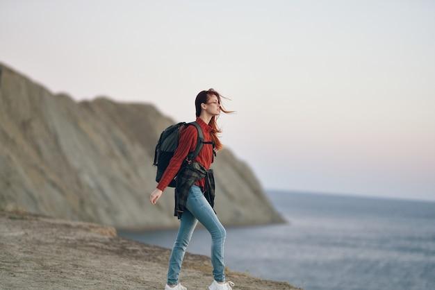 Женщина в горах на открытом воздухе у моря на пляже с рюкзаком на спине