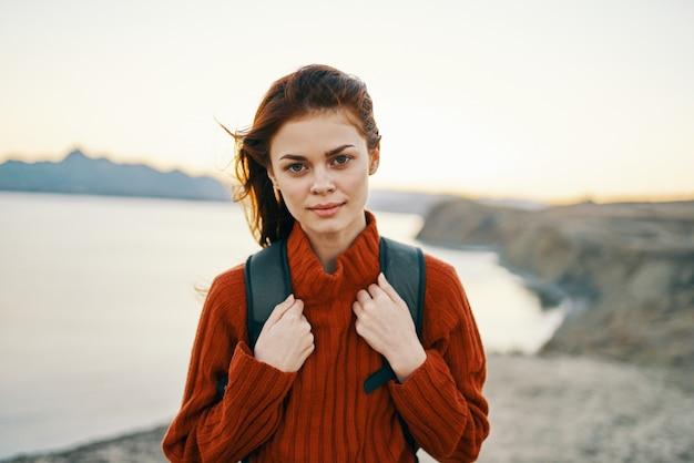 Женщина в горах на открытом воздухе отдыхает на берегу моря, пляж песок рюкзак свежий воздух. фото высокого качества