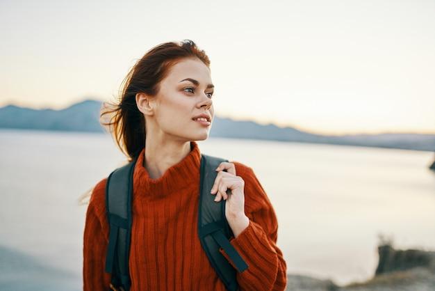 Женщина в горах на открытом воздухе отдыхает у моря, пляжный песочный рюкзак, свежий воздух