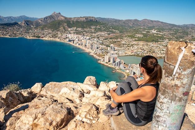 街を見ながら岩の上に座っている山の女性