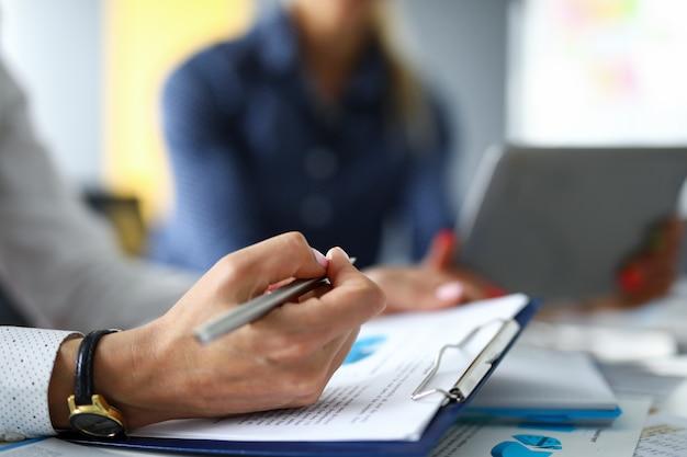 オフィスの女性は、テーブルでペンの女性と話し合ってレポートにメモを取ります