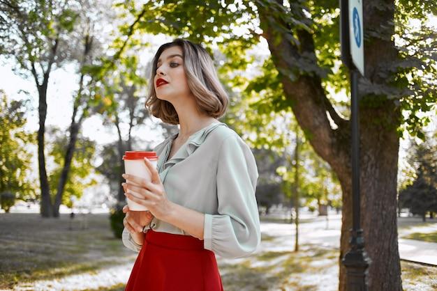 公園の女性一杯の飲み物散歩休憩木