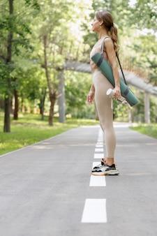 夏の公園の女性はヨガのトレーニングに行きます