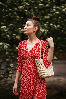 夏の籐のバッグが付いている公園の女性。赤いドレス