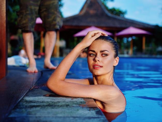 贅沢な休暇の自然熱帯旅行を日焼けするプールの女性