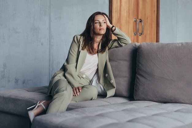 スーツを着た女性が思慮深くソファに座ります。