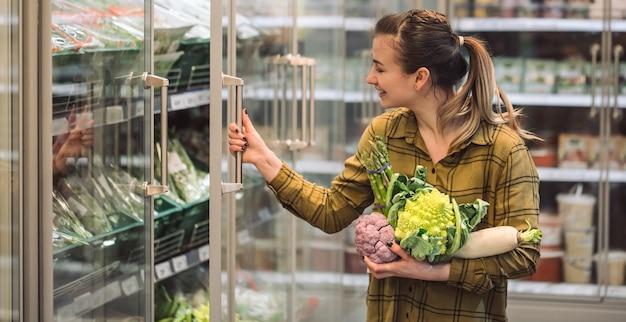 Женщина в супермаркете. красивая молодая женщина держит в руках свежие органические овощи и открывает холодильник в супермаркете. концепция здорового питания. урожай